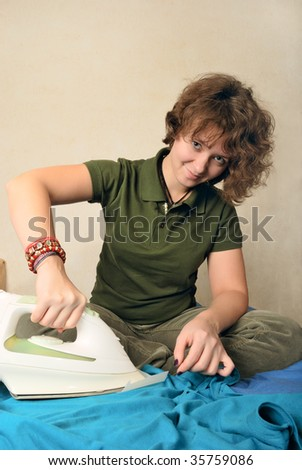 Girl removing vax candle stains with iron and tracing paper - stock photo