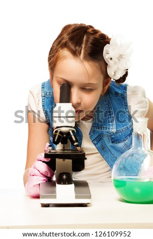Girl researching looking into microscope with lab tubes - stock photo