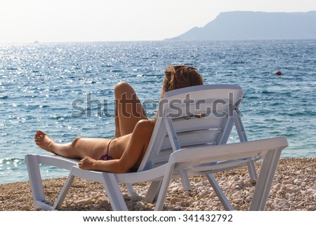 Girl resting in a deck chair and watching the sea. Tourism