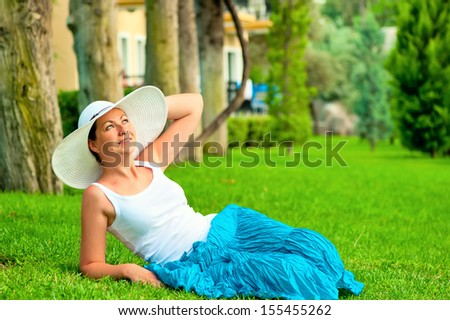 Girl resting on the lawn and looking up - stock photo