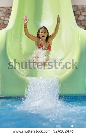 Girl rides on the water slide in a water park.