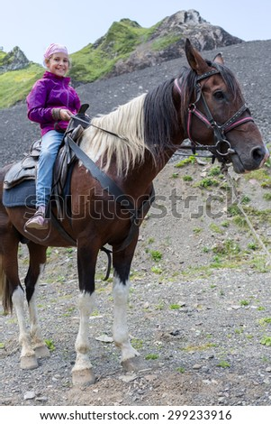 girl riding a horse in the mountains - stock photo