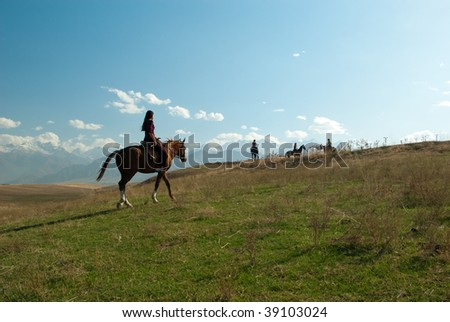 Girl riding a horse in the mountains with a group of rider waiting for her - stock photo