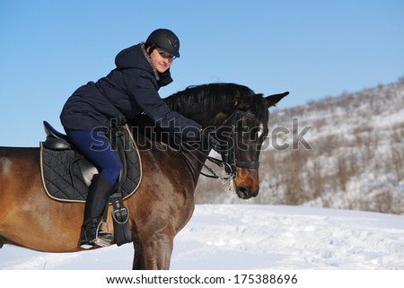 Girl riding a horse in winter field - stock photo