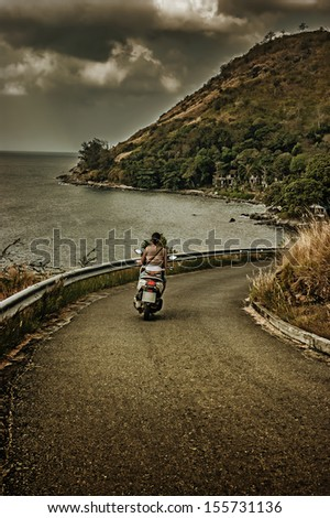 girl riding a motorcycle on a country road - stock photo