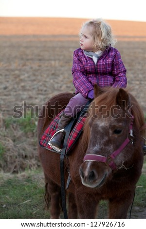 Girl Riding a Pony - baby Ride a Horse. Lonely young cute lovely girl is riding a pretty pony horse alone. sundown in the background