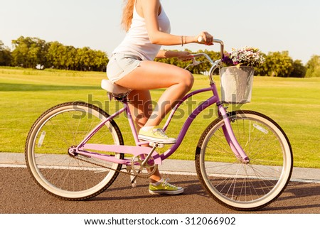 girl riding on a bicycle with flowers - stock photo