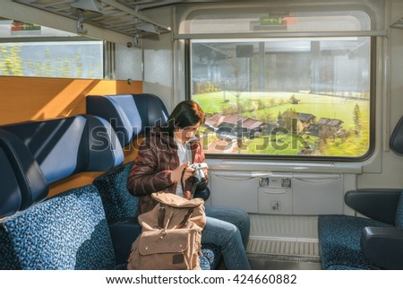 Girl riding on a train and watching pictures on the camera. View outside the window. Traveling by train at the Alpine Railroad