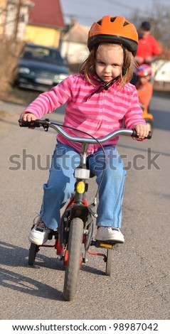 girl riding on his first bike in a helmet - stock photo