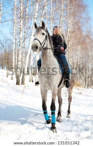 Girl riding on pale horse in sunny winter birch forest - stock photo