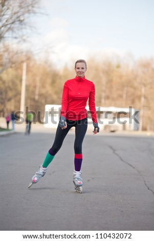 Girl roller-skating on the road - stock photo