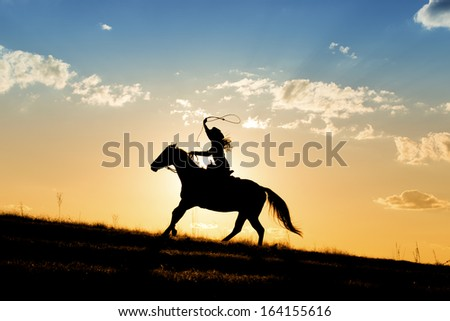 Girl roping while riding hose with beautiful sunset behind her  - stock photo