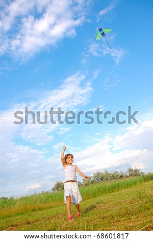girl running and flying a kite in the meadow - stock photo