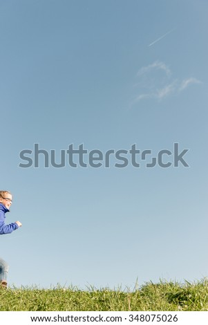 Girl running in front of blue sky - stock photo