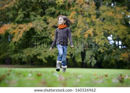 girl running in the park in autumn - stock photo