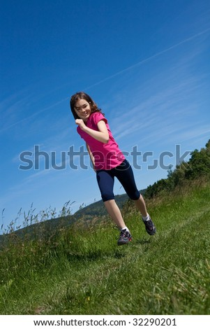 Girl running on green meadow against blue sky
