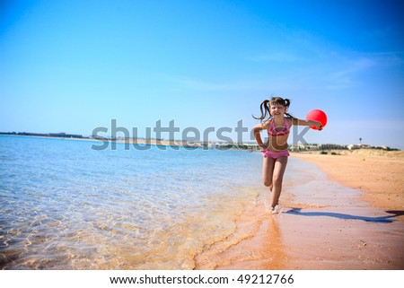 Girl Running on sunny beach with red balloon - stock photo
