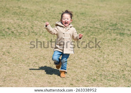 Girl running on the lawn - stock photo