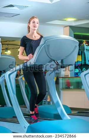 Girl running on the treadmill at the gym. Athletes wearing sportswear and running in the gym front view of athletes. - stock photo