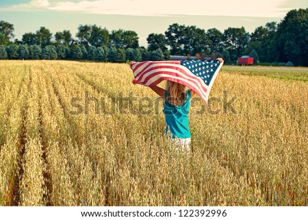 girl running with wheat field with American flag - stock photo