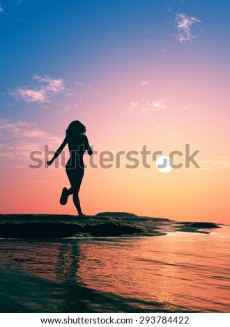 Girl runs along the beach at sunset.