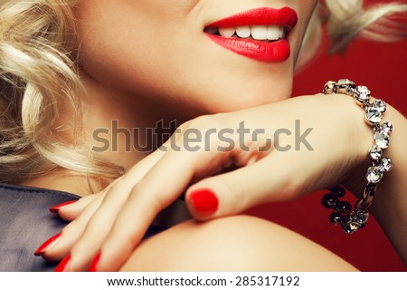 Girl's best friends and femme fatale concept. Marilyn Monroe style. Close up portrait of rich young woman smiling wearing expensive luxurious diamond bracelet. Studio shot