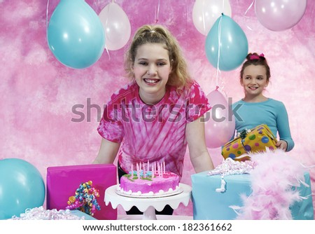 Girl's birthday party celebration with cake and balloons with girl in background watching friend preparing to blow out candles - stock photo