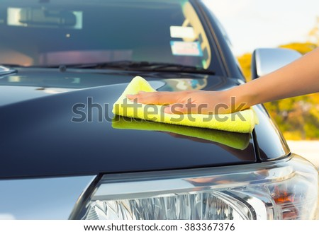 Girl's hand wiping on surface of car shine. - stock photo