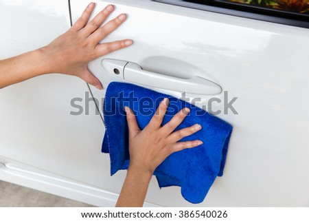 Girl's hand wiping on surface of white car.  - stock photo