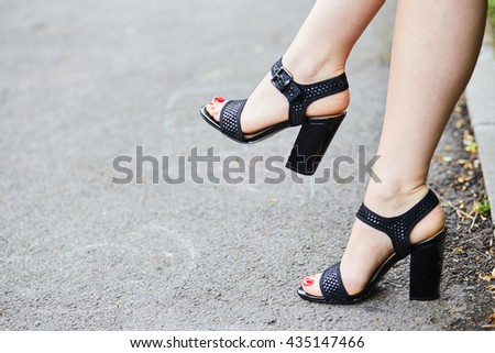 Girl's legs wearing black sandals sitting on a bench with the legs crossed, space for text - stock photo
