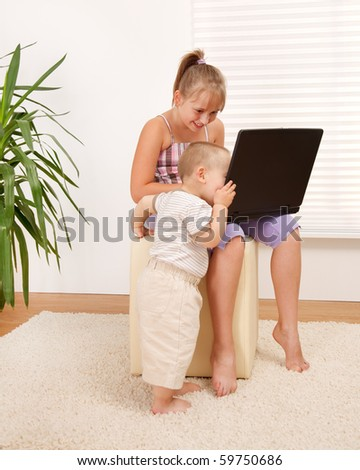Girl's little brother looking close into the laptop screen - stock photo