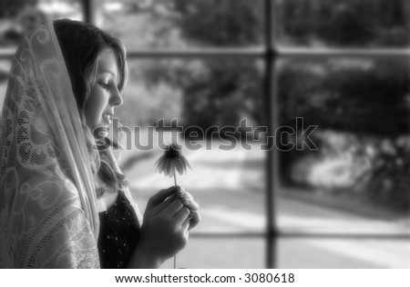 Girl's profile by window, wearing a shawl on her head, looking at an echinacea flower, black and white - stock photo