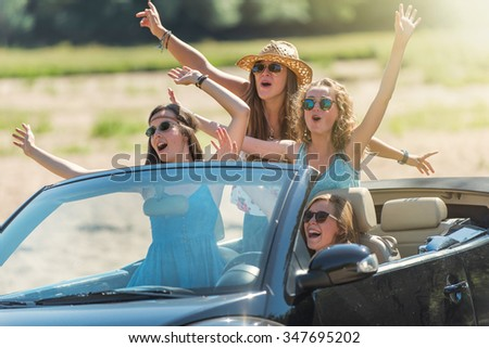 Girl's weekend ! Four young women are having fun in a black convertible on a country road by a sunny day. They are wearing summer clothes, hats, and sunglasses and singing with their hands in the air - stock photo