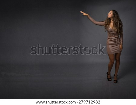 girl say hello with hand, dark background - stock photo