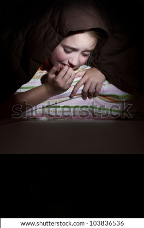 Girl scared in her bed at nighttime imagining monsters under bed - stock photo