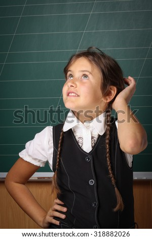 Girl schoolgirl in a black school uniform, a white shirt with two pigtails on a green blackboard