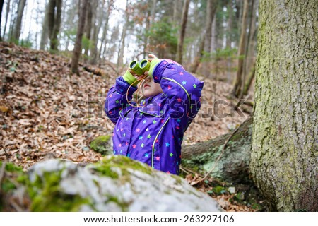 Girl scout looking through the binoculars in a forest, inspecting the surroundings and bird watching  - stock photo