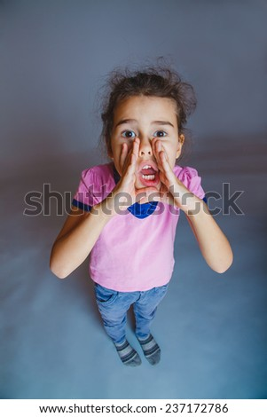 Girl screams leaning hand over his mouth - stock photo