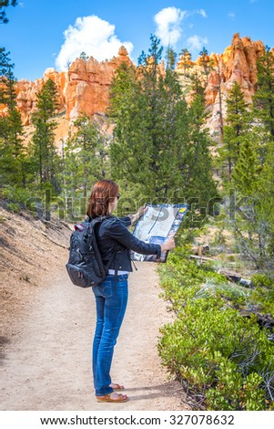 Girl searching right direction on map in Bryce Canyon, USA - stock photo