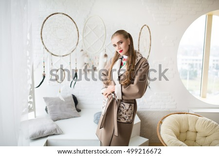 Girl seating near creative round dream catchers. Big white wall background. Beautiful Young sexual pretty woman waits. Long black stylish jacket hot autumn. Vintage stylistic room decorative accessory