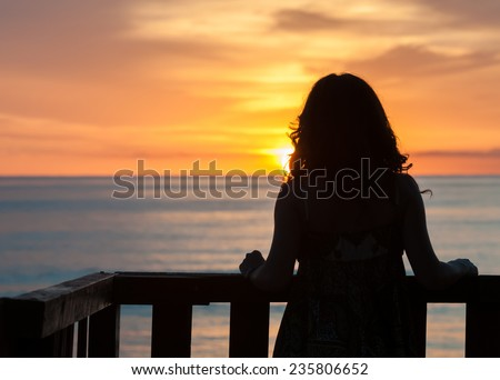Girl seen from behind standing on a balcony in front of the sea and looking the sunrise - stock photo