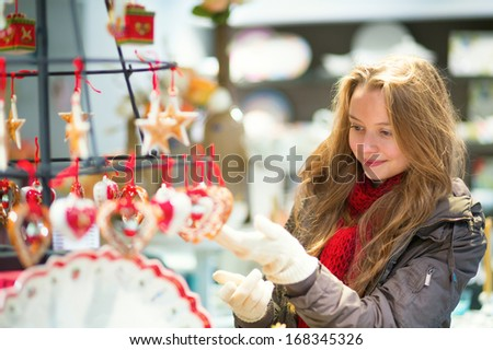Girl selecting decoration on a Christmas market - stock photo