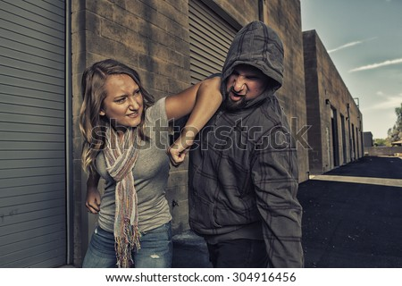 GIRL SELF DEFENSE | A young woman defends herself against a male attacker in an alley by elbowing him in the jaw. Refuse to be a victim.    - stock photo