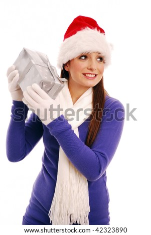 Girl shaking christmas gift to guess what it is - stock photo