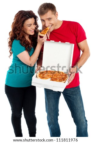 Girl sharing a pizza piece with her boyfriend. making him eat from her hands. Love couple - stock photo