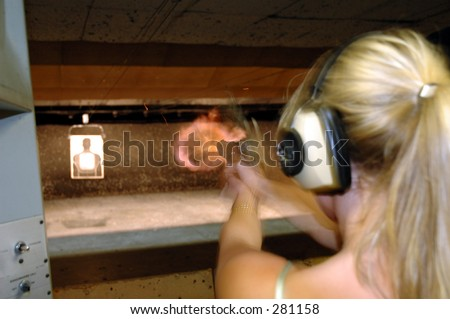 Girl shoots an gun range. - stock photo