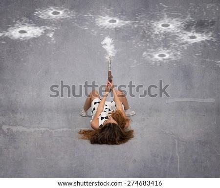 girl shot with gun on an empty space, dark background - stock photo