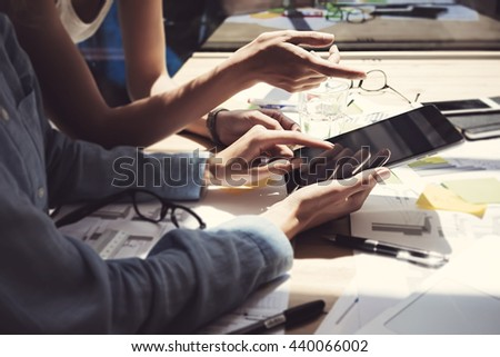 Girl Showing Screen Digital Tablet Hand.Project Managers Researching Process.Business Team Working Startup modern Office.Analyze market stock.Using electronic devices,papers,notes wood table.Blurred - stock photo