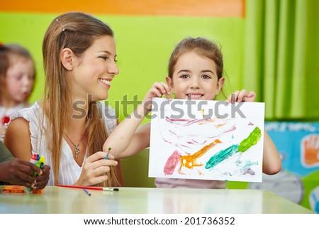 Girl showing self drawn painting in kindergarten with nursery teacher - stock photo
