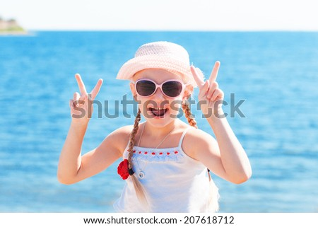 girl showing sign victory with fingers near sea - stock photo